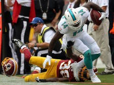 LANDOVER, MD - SEPTEMBER 13: Wide receiver Jarvis Landry #14 of the Miami Dolphins is pushed out of bounds by defensive back Dashon Goldson #38 of the Washington Redskins in the second half during a game at FedExField on September 13, 2015 in Landover, Maryland. (Photo by Patrick Smith/Getty Images)