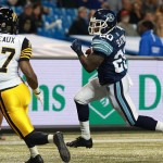 TORONTO, ON - OCTOBER 10:  Delvin Breaux #27 of the Hamilton Tiger-Cats look on as Steve Slaton #20 of the Toronto Argonauts runs the ball in for a touchdown during their game at Rogers Centre on October 10, 2014 in Toronto, Canada. (Photo by Dave Sandford/Getty Images)