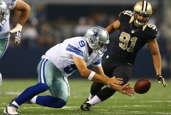 ARLINGTON, TX - SEPTEMBER 28:  Tony Romo #9 of the Dallas Cowboys recovers a loose ball as Kasim Edebali #91 of the New Orleans Saints defends in the second half at AT&T Stadium on September 28, 2014 in Arlington, Texas.  (Photo by Ronald Martinez/Getty Images)