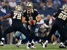 ARLINGTON, TX - SEPTEMBER 28:  Drew Brees #9 of the New Orleans Saints looks to hand off against the Dallas Cowboys in the first half at AT&T Stadium on September 28, 2014 in Arlington, Texas.  (Photo by Tom Pennington/Getty Images)