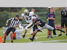 New Orleans Saints wide receiver Joseph Morgan (13) stretches to the end zone as New England Patriots cornerback Malcolm Butler (21) tries to make the stop during a joint practice at the Saints' NFL football training camp in White Sulphur Springs, W.Va., Wednesday, Aug. 19, 2015.  (AP Photo/Steve Helber)