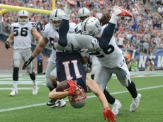 FOXBORO, MA - SEPTEMBER 21: Julian Edelman #11 of the New England Patriots is tackled during the fourth quarter against the Oakland Raiders at Gillette Stadium on September 21, 2014 in Foxboro, Massachusetts. (Photo by Darren McCollester/Getty Images) *** BESTPIX ***