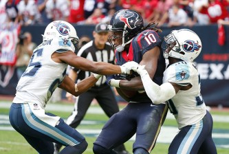 HOUSTON, TX - NOVEMBER 30: DeAndre Hopkins #10 of the Houston Texans is tackled by Blidi Wreh-Wilson #25 and Jason McCourty #30 of the Tennessee Titans in the fourth quarter in a NFL game on November 30, 2014 at NRG Stadium in Houston, Texas. (Photo by Scott Halleran/Getty Images)
