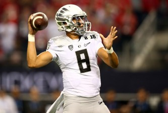 ARLINGTON, TX - JANUARY 12:  Quarterback Marcus Mariota #8 of the Oregon Ducks throws the ball against the Ohio State Buckeyes during the College Football Playoff National Championship Game at AT&T Stadium on January 12, 2015 in Arlington, Texas.  (Photo by Ronald Martinez/Getty Images)