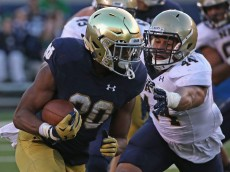 SOUTH BEND, IN - OCTOBER 10:  C.J. Prosise #20 of the Notre Dame Fighting Irish runs for a first down past Micah Thomas #44 of the Navy Midshipmen  at Notre Dame Stadium on October 10, 2015 in South Bend, Indiana. Notre Dame defeated Navy 41-24.  (Photo by Jonathan Daniel/Getty Images)