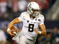 ARLINGTON, TX - JANUARY 12:  Quarterback Marcus Mariota #8 of the Oregon Ducks runs the ball against the Ohio State Buckeyes during the College Football Playoff National Championship Game at AT&T Stadium on January 12, 2015 in Arlington, Texas.  (Photo by Ronald Martinez/Getty Images)