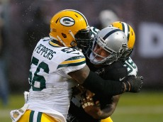 OAKLAND, CA - DECEMBER 20: Quarterback Derek Carr #4 of the Oakland Raiders is sacked by line backer Mike Neal #96 and line backer Julius Peppers #56 of the Green Bay Packers in the fourth quarter at O.co Coliseum on December 20, 2015 in Oakland, California. (Photo by Lachlan Cunningham/Getty Images)