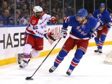 Mar 29, 2015; New York, NY, USA; New York Rangers center Dominic Moore (28) controls the puck in front of Washington Capitals right wing Joel Ward (42) during the first period at Madison Square Garden. Mandatory Credit: Adam Hunger-USA TODAY Sports