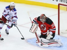 Oct 21, 2014; Newark, NJ, USA; New Jersey Devils goalie Cory Schneider (35) makes a save while New York Rangers right wing Mats Zuccarello (36) looks for the rebound during third period at Prudential Center. The Rangers defeated the Devils 4-3 in overtime.  Mandatory Credit: Ed Mulholland-USA TODAY Sports