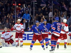 Oct 16, 2014; New York, NY, USA; New York Rangers center Derick Brassard (16) celebrates scoring a goal on Carolina Hurricanes goalie Anton Khudobin (31) with defenseman Dan Girardi (5) and right wing Mats Zuccarello (36) during the third period at Madison Square Garden. The Rangers defeated the Hurricanes 2-1. Mandatory Credit: Adam Hunger-USA TODAY Sports