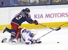 Columbus Blue Jackets right wing Cam Atkinson (13) trips over New York Rangers center Derick Brassard (16) chasing after the puck during the second period of the NHL hockey game between the Columbus Blue Jackets and the New York Rangers at Nationwide Arena in Columbus, Ohio, on Friday, March 21, 2014. After two periods the score was tied at 0.  (Columbus Dispatch/Sam Greene)