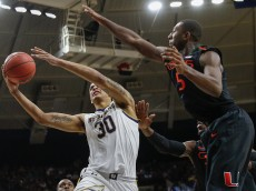 SOUTH BEND, IN - JANUARY 17: Zach Auguste #30 of the Notre Dame Fighting Irish shoots the ball as Davon Reed #5 of the Miami (Fl) Hurricanes guards at Purcell Pavilion on January 17, 2015 in South Bend, Indiana. Notre Dame defeated Miami 75-70. (Photo by Michael Hickey/Getty Images)