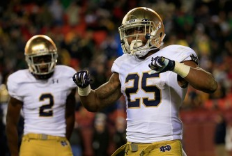 LANDOVER, MD - NOVEMBER 01:  Running back Tarean Folston #25 of the Notre Dame Fighting Irish celebrates after rushing for a fourth quarter touchdown against the Navy Midshipmen at FedExField on November 1, 2014 in Landover, Maryland.  (Photo by Rob Carr/Getty Images)