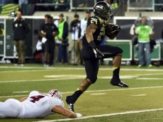 EUGENE, OR - NOVEMBER 1: Running back Thomas Tyner #24 of the Oregon Ducks avoids the tackle of linebacker Blake Martinez #4 of the Stanford Cardinal as he runs for a touchdown during the third quarter of the game at Autzen Stadium on November 1, 2014 in Eugene, Oregon. The Ducks won the game 45-16. (Photo by Steve Dykes/Getty Images)
