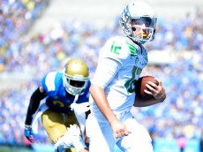 PASADENA, CA - OCTOBER 11:  Taylor Alie #12 of the Oregon Ducks runs in to score a two point conversion during the first quarter against the UCLA Bruins at Rose Bowl on October 11, 2014 in Pasadena, California.  (Photo by Harry How/Getty Images)