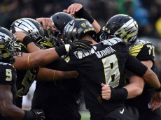 EUGENE, OR - NOVEMBER 1: Quarterback Marcus Mariota #8 of the Oregon Ducks celebrates with his teammates after scoring a touch down during the first quarter of the game against the Stanford Cardinal at Autzen Stadium on November 1, 2014 in Eugene, Oregon. (Photo by Steve Dykes/Getty Images)