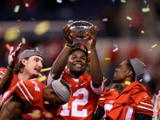 INDIANAPOLIS, IN - DECEMBER 06:  Quarterback Cardale Jones #12 of the Ohio State Buckeyes lifts the Big Ten trophy after his team defeeated the Wisconsin Badgers 59-0 in the Big Ten Championship at Lucas Oil Stadium on December 6, 2014 in Indianapolis, Indiana.  (Photo by Andy Lyons/Getty Images)