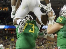 SANTA CLARA, CA - DECEMBER 5:  Royce Freeman #21 of the Oregon Ducks celebrates a 37-yard touchdown with outside lineman Tyrell Crosby #73 which was nullified by a holding call in favor of the Arizona Wildcats in the first quarter on December 5, 2014 during the Pac-12 Championship at Levi's Stadium in Santa Clara, California.  Oregon won 51-13.  (Photo by Brian Bahr/Getty Images)