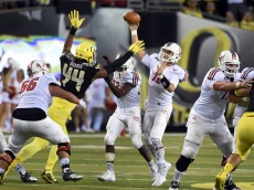 EUGENE, OR - SEPTEMBER 05:  Quarterback Reilly Hennessey #12 of the Eastern Washington Eagles passes the ball under pressure from defensive lineman DeForest Buckner #44 of the Oregon Ducks during the fourth quarter of the game at Autzen Stadium on September 5, 2015 in Eugene, Oregon.  (Photo by Steve Dykes/Getty Images)