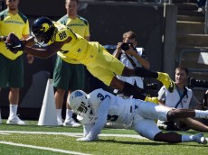 EUGENE, OR - SEPTEMBER 19: Wide receiver Dwayne Stanford #88 of the Oregon Ducks dives over safety Tarris Batiste #3 of the Georgia State Panthers for a touchdown during the second quarter of the game at Autzen Stadium on September 19, 2015 in Eugene, Oregon.  (Photo by Steve Dykes/Getty Images)