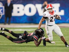 Dec 30, 2014; Charlotte, NC, USA; Georgia Bulldogs running back Nick Chubb (27) stiff arms Louisville Cardinals cornerback Terell Floyd (19) during the first quarter of the Belk Bowl held at Bank of America Stadium. Mandatory Credit: Jeremy Brevard-USA TODAY Sports
