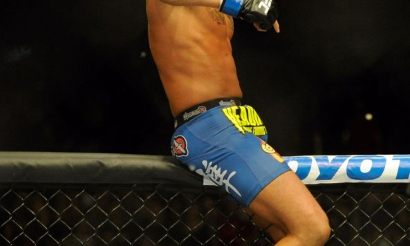Anthony Pettis celebrates his UFC 164 victory over Benson Henderson on top of the cage
