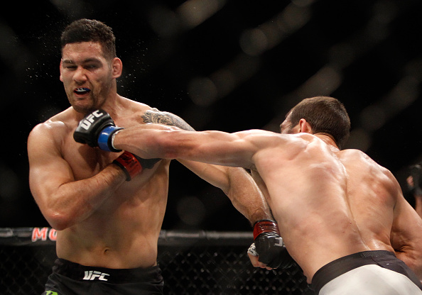LAS VEGAS, NV - DECEMBER 12:  Chris Weidman (L) takes a punch from Luke Rockhold in their middleweight title fight during UFC 194 at MGM Grand Garden Arena on December  12, 2015 in Las Vegas, Nevada.  (Photo by Steve Marcus/Getty Images)