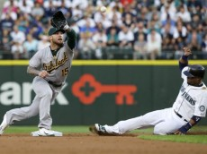 Oakland Athletics third baseman Brett Lawrie reaches to catch the pick-off throw as Seattle Mariners' Robinson Cano, right, attempts to steal second base in the second inning of a baseball game, Monday, Aug. 24, 2015, in Seattle. Lawrie's tag on Cano was ruled an out after the initial safe call on the field was challenged by the Athletics. (AP Photo/Ted S. Warren)