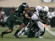 Oregon's Royce Freeman, right, is tackled by Michigan State's Darien Harris (45) and Arjen Colquhoun, left, during the first quarter of an NCAA college football game, Saturday, Sept. 12, 2015, in East Lansing, Mich. (AP Photo/Al Goldis)