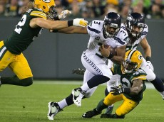 Seahawks quarterback Russell Wilson picks up a first down with Packers safety Morgan Burnett on him in the first quarter as the Seahawks take on the Green Bay Packers at Lambeau Field in Green Bay, Wisconsin Sunday September 20, 2015.   (Bettina Hansen / The Seattle Times)