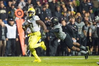 Oregon Ducks running back Royce Freeman (21) escapes the tackle of Colorado Buffaloes defensive back Chidobe Awuzie (4) while running the ball down the field during the first quarter. The Oregon Ducks play the Colorado Buffaloes at Folsom Field in Boulder, Colorado, on October 3, 2015. (Taylor Wilder/Emerald)