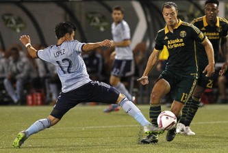 Sporting KC midfielder Mikey Lopez, left, taps ball away from Portland Timbers defender/midfielder Jack Jewsbury, right, during the first half of an MLS soccer match in Portland, Ore., Saturday, Oct. 3, 2015. (AP Photo/Steve Dipaola)