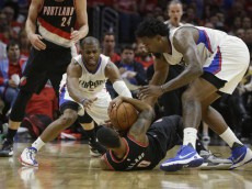 Portland Trail Blazers' Damian Lillard, center, grabs a loose ball against Los Angeles Clippers' DeAndre Jordan, right, and Chris Paul in the first half in Game 1 of a first-round NBA basketball playoff series, on Sunday, April 17, 2016, in Los Angeles. (AP Photo/Jae C. Hong)
