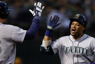 Seattle Mariners' Robinson Cano, right, celebrates with Adam Lind (26) after hitting a home run off Oakland Athletics' Sonny Gray in the fourth inning of a baseball game Tuesday, May 3, 2016, in Oakland, Calif. (AP Photo/Ben Margot)