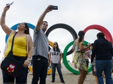 TOPSHOT - Olympic fans take photographs and pose for selfies in front of the Olympic rings on Copacabana beach in Rio de Janeiro, on 30 July 2016.  The city is making last minute preparations for the events and celebrations as the 2016 Rio Olympic Games are set to begin in Rio on August 5 and run until August 21, 2016. / AFP / LEON NEAL        (Photo credit should read LEON NEAL/AFP/Getty Images)