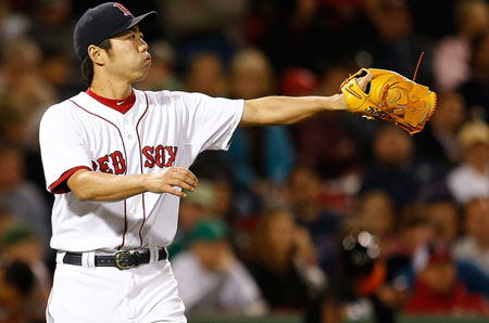 Koji Uehara #19 of the Boston Red Sox reacts after giving up a triple to Danny Valencia #35 of the Baltimore Orioles in the ninth inning at Fenway Park on September 17 in Boston, Massachusetts.