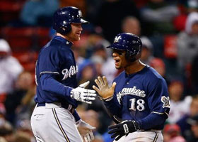 Khris Davis #18 of the Milwaukee Brewers celebrates with teammate Lyle Overbay #24 after scoring the go-ahead run in the 11th inning off of an RBI double by Logan Schafer #1 of the Milwaukee Brewers against the Boston Red Sox during the game at Fenway Park on April 5, 2014 in Boston, Massachusetts.