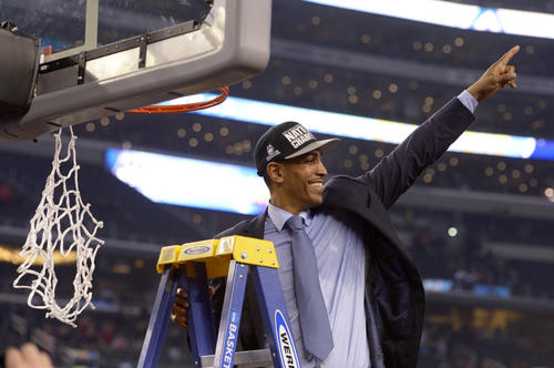 UConn coach Kevin Ollie celebrates after the win and before cutting down the net.