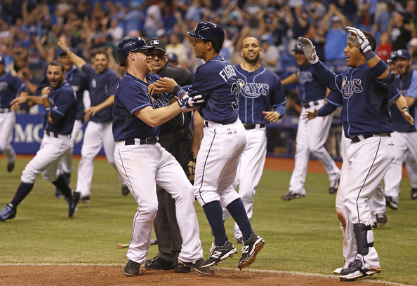 Logan Forsythe (L) and Yunel Escobar (R) come in to celebrate with Cole Figueroa #35 of the Tampa Bay Rays after Figueroa scored off a one-run game-winning fielder's choice by the Rays' Desmond Jennings to end the 15th inning of a game against the Boston Red Sox on May 24, 2014 at Tropicana Field in St. Petersburg, Florida.