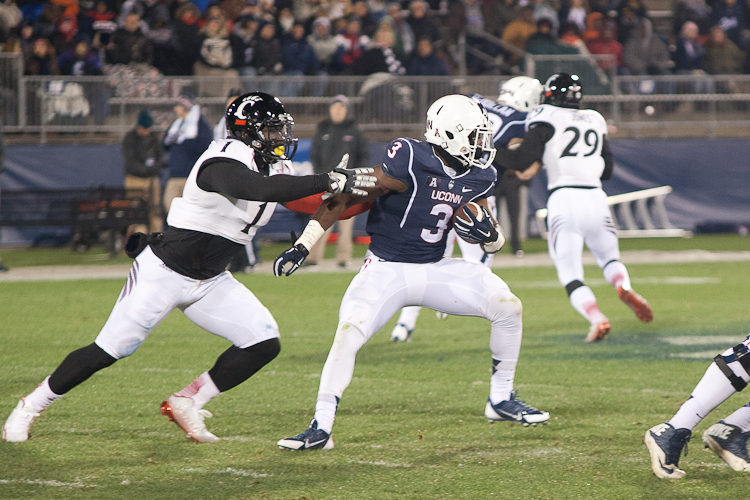 UConn RB Ron Johnson (3) spins to avoid the tackle of Cincinnati LB Jeff Luc (1) at Rentschler Field on November 22, 2014.