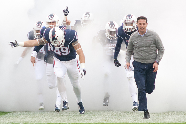 UConn Football Coach Bob Diaco leads his team onto the field before the game against the UCF Knights at Rentschler Field on Saturday, November 1, 2014.