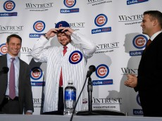 CHICAGO, IL - DECEMBER 15:  Pitcher Jon Lester (C) puts on a Cubs hat during an introduction press conference as Chicago Cubs President Theo Epstein (R) and general manager Jed Hoyer looks on on December 15, 2014  in Chicago, Illinois. (Photo by David Banks/Getty Images)