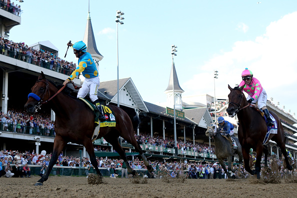 LOUISVILLE, KY - MAY 02:  Jockey Victor Espinoza celebrates as he guides American Pharoah #18 ahead of Firing Line #10, ridden by Gary Stevens, after crossing the finish line to win the 141st running of the Kentucky Derby at Churchill Downs on May 2, 2015 in Louisville, Kentucky.  (Photo by Rob Carr/Getty Images)
