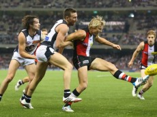 MELBOURNE, AUSTRALIA - MAY 12:  Clinton Jones of the Saints kicks whilst being tackled by Brock McLean of the Blues during the round eight AFL match between the St Kilda Saints and the Carlton Blues at Etihad Stadium on May 12, 2014 in Melbourne, Australia.  (Photo by Quinn Rooney/Getty Images)
