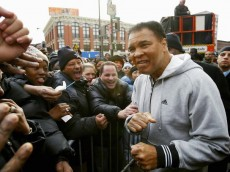 NEW YORK CITY - FEBRUARY 5:  Boxing legend Muhammad Ali greets the crowd before he unveils a new wallscape for addidas with his daughter, Laila Ali, on February 5, 2003 in Harlem, New York City. (Photo by Ezra Shaw/Getty Images)