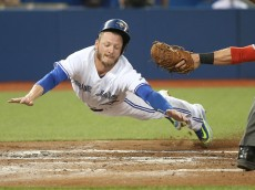 TORONTO, CANADA - SEPTEMBER 2: Josh Donaldson #20 of the Toronto Blue Jays slides safely across home plate to score on a sacrifice fly in the second inning during MLB game action as Yan Gomes #10 of the Cleveland Indians reaches with an attempted tag on September 2, 2015 at Rogers Centre in Toronto, Ontario, Canada. (Photo by Tom Szczerbowski/Getty Images) *** Local Caption *** Josh Donaldson; Yan Gomes