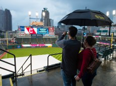 CLEVELAND, OH - SEPTEMBER 11: Fans Richard and Jodi Tattoni shoot a photo of rain soaked Progressive Field on September 11, 2015 in Cleveland, Ohio. The game between the Detroit Tigers and Cleveland Indians was postponed due to weather. (Photo by Jason Miller/Getty Images)