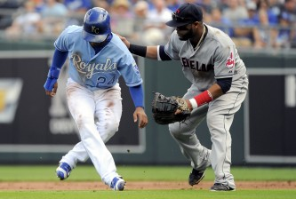 KANSAS CITY, MO - SEPTEMBER 27:  Christian Colon #24 of the Kansas City Royals is tagged out by Carlos Santana #41 of the Cleveland Indians as he is picked off on a steal attempt in the third inning at Kauffman Stadium on September 27, 2015 in Kansas City, Missouri. (Photo by Ed Zurga/Getty Images)