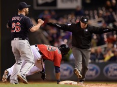 MINNEAPOLIS, MN - APRIL 25: Mike Napoli #26 of the Cleveland Indians reacts as umpire Doug Eddings #88 calls Danny Santana #39 of the Minnesota Twins safe after a dive back to first base during the fifth inning of the game on April 25, 2016 at Target Field in Minneapolis, Minnesota. The Indians challenged the call and the call stood. (Photo by Hannah Foslien/Getty Images)