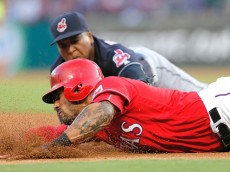 ARLINGTON, TX - AUGUST 27: Ian Desmond #20 of the Texas Rangers dives to tag up on third as third baseman Jose Ramirez #11 of the Cleveland Indians is unable to make the tag during the first inning of a baseball game at Globe Life Park on August 27, 2016 in Arlington, Texas. (Photo by Brandon Wade/Getty Images)